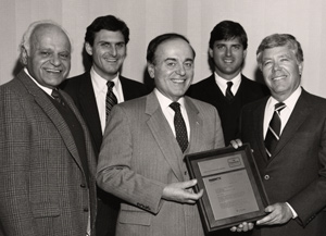 1986 ­ Al Jordan, President of Fabritec International, presenting a plaque to Arthur Anton, Sr., commemorating Anton's 50 years as a Sanitone licensee. From left to right: Owners Soc and Arthur Anton with Al Jordan. Sons Charles and Arthur in background represent the third generation in the family business.